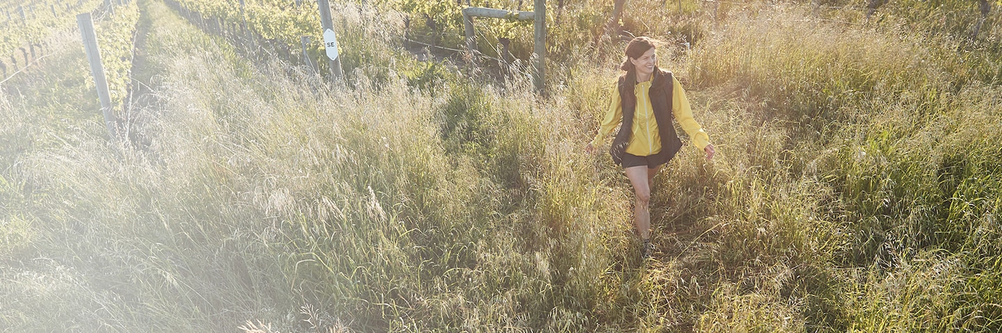 woman wearing a yellow jacket and hiking in a field