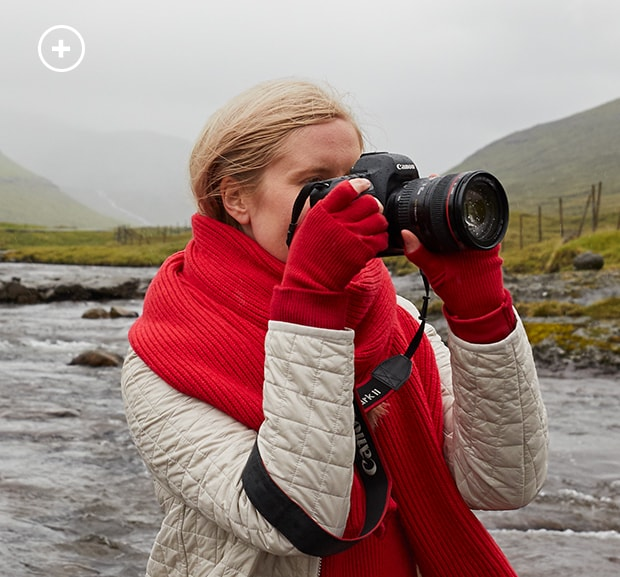 woman wearing red turtle neck and dove grey recycled jacket and hunter boots in a pond