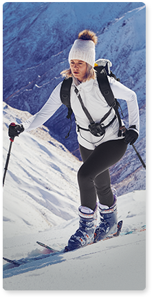 woman wearing white jacket, beanie and black tights skiing in the mountains