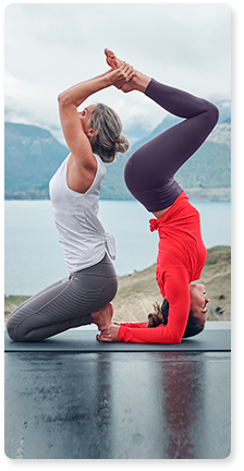 two women wearing gray tights and white tank and orange long sleeve doing a yoga pose together