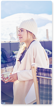 woman wearing cozy sweater and white beaner holding a coffee mug