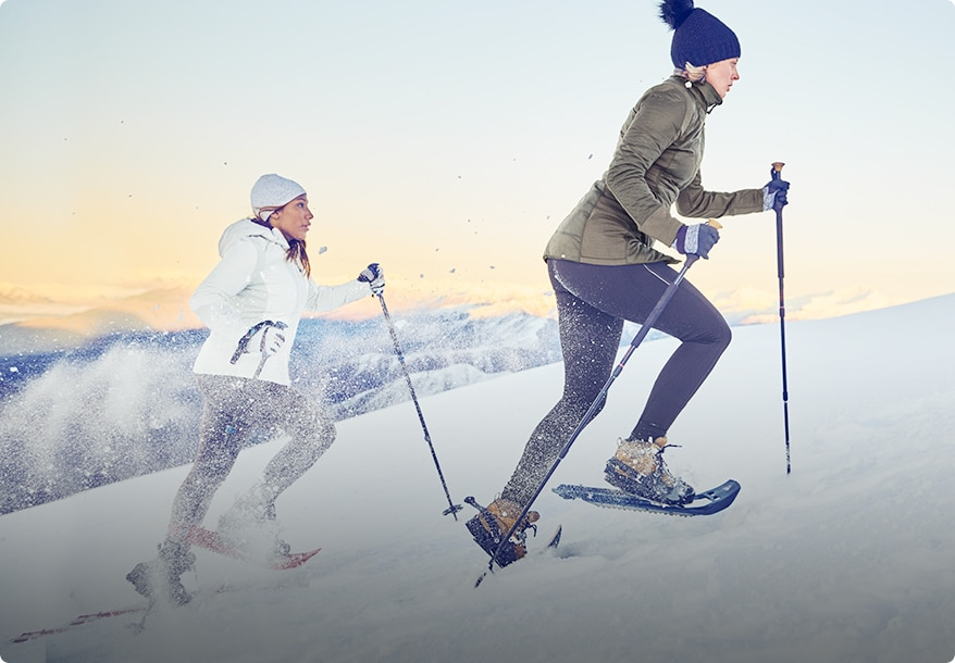 two women wearing cold weather training attire and skiing in the mountains