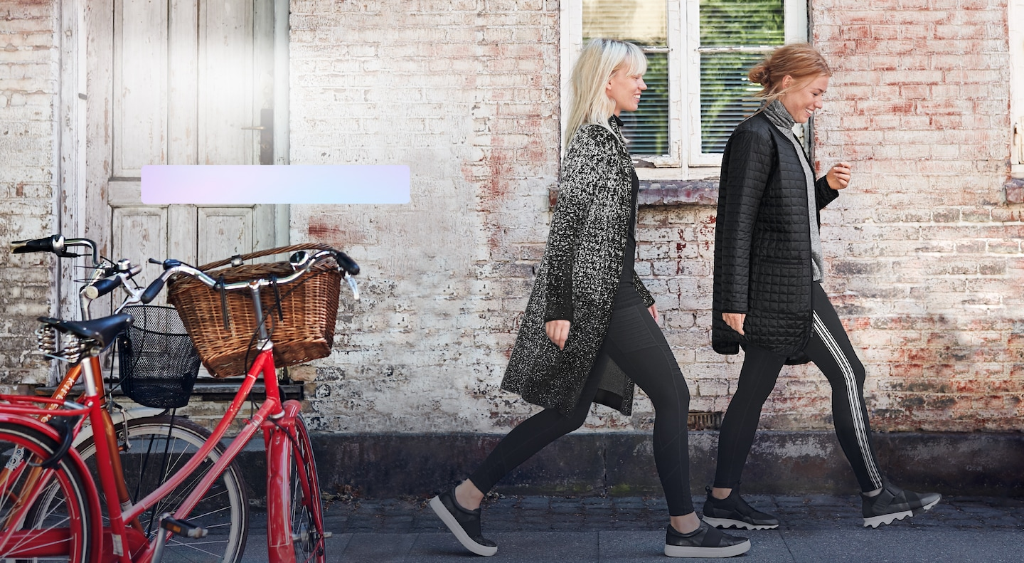 one women wearing long grandview jacket and women wearing long jacket and commute tights walking together