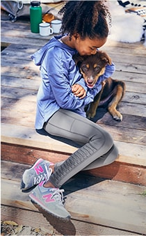 girl wearing blue and grey tights hugging her dog