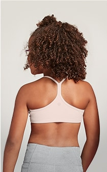 girl facing backwards wearing light pink sports bra