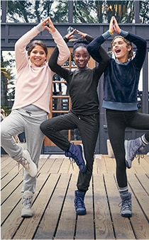 three girl wearing various colors of sweater doing the same yoga pose