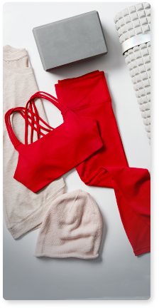 flat lay of white sweater and red sports bra and tights