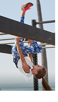 girl wearing white top and blue floral print tights hanging upside down on monkey bars