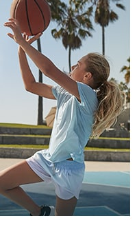 girl wearing short sleeve tee and shorts and shooting basketball