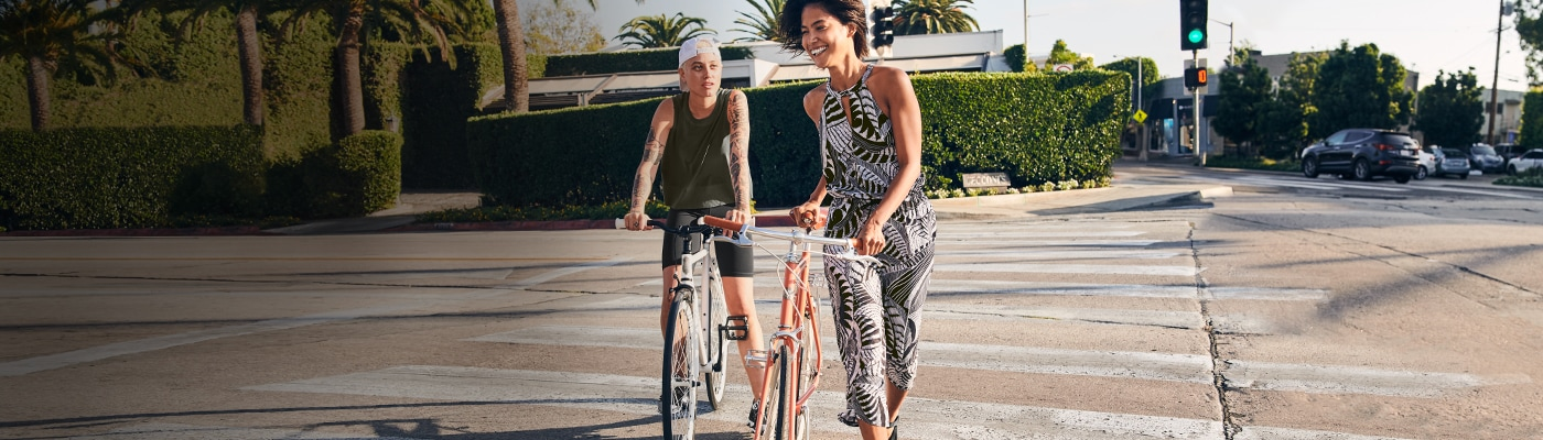 woman wearing floral romper and walking her bike with a friend