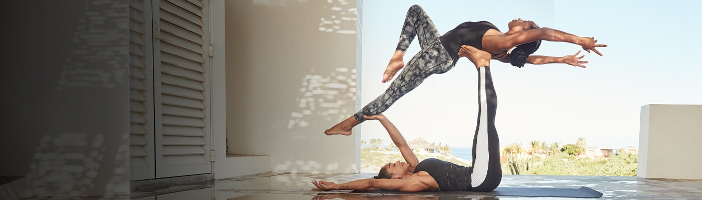 two women wearing powervita and doing acro yoga