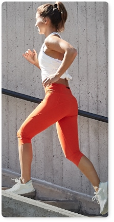 woman wearing orange velocity crop tights and white tank top running