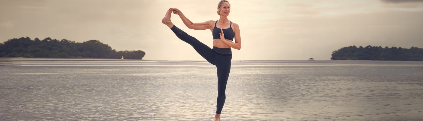 woman wearing navy elevation 7/8 tight doing yoga on the beach