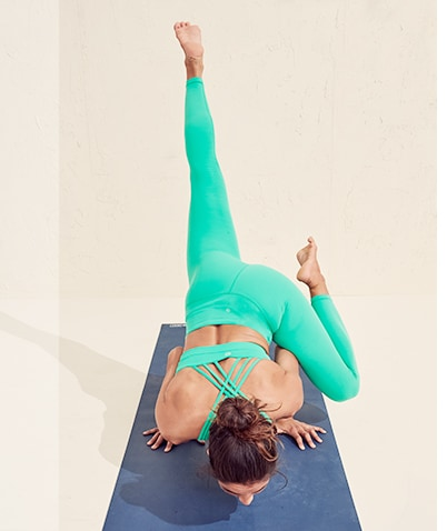 woman in teal powervita tights and sports bra matching set doing yoga