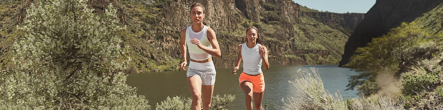 two women running uphill in white tanks the the running free 3.5 inch short