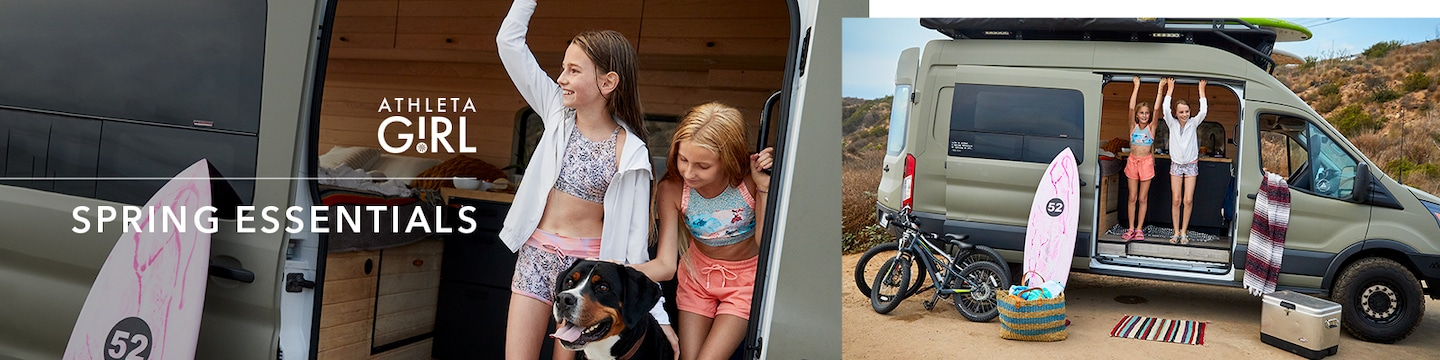 Girls hanging out of a camper van with dog and surfboard